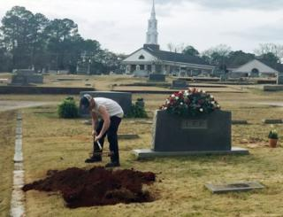A man rakes soil over a grave in the Lee family cemetery plot, Saturday, 20 February, 2016, in Monroeville, Alabama.
