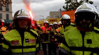 Firefighters hold placards and a smoke-bomb as they take part in a demonstration to protest against the pension overhauls, in Marseille, southern France, on 5 December, 2019