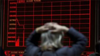 A woman reacts near a display board showing the plunge in the Shanghai Composite Index at a brokerage in Beijing, China, Thursday, Jan. 7, 2016