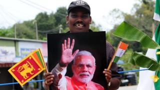 A Sri Lankan ethnic Tamil holds memorabilia bearing the portrait of Indian Prime Minister Narendra Modi as he waits for his arrival in a ceremony to hand over Indian-funded houses to Tamils displaced or made destitute by fighting in Jaffna, some 400 kilometres (250 miles) north of Colombo on March 14, 2015. Narendra Modi landed in Jaffna on March 14, becoming the first Indian prime minister to visit Sri Lanka's war-ravaged northern Tamil heartland. AFP PHOTO / Lakruwan WANNIARACHCHI (Photo credit should read LAKRUWAN WANNIARACHCHI/AFP/Getty Images)