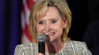 Cindy Hyde-Smith holds a microphone