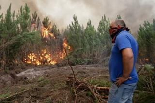 A member of the public helping firefighting efforts looks at a forest fire in Gaeiras, Marinha Grande, in central Portugal 16/10/2017