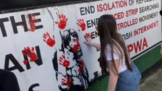 A woman smears a red hand print on a wall