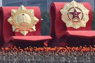 A float with an emblem of the Chinese People's Liberation Army (R) passes through Tiananmen Square during the National Day parade in Beijing on 1 October 2019, to mark the 70th anniversary of the founding of the Peoples Republic of China.