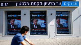 A man cycles past images of Donald Trump displayed on monitors in Tel Aviv, Israel (9 November 2016)