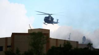 A Salvadoran army helicopter flies over the ministry of treasury building during a blaze in San Salvador, El Salvador, July 7, 2017.