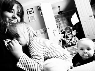A black-and-white photo of a woman at home with two children