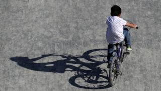 A boy rides a bicycle in a park in Brussels as Belgium remains under lockdown