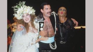 Jane Seymour dalam gaun Emanuel, bersama Freddie Mercury dan seorang teman di acara amal Fashion Aid pada 1985.