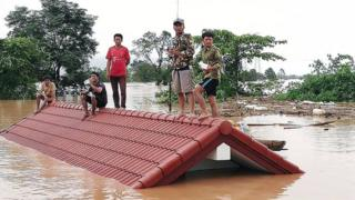 Laos villagers are stranded on a roof of a house.