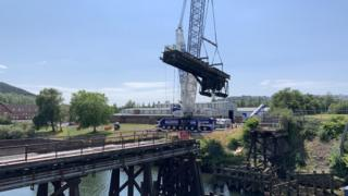 Crane lifts bridge section from its footings