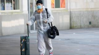A Traveller attends Cardiff Central Station with face mask and protective body suit