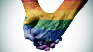 Two men holding hands with the rainbow flag projected onto them