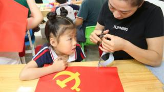 A schoolgirl makes a flag of the Communist Party of China