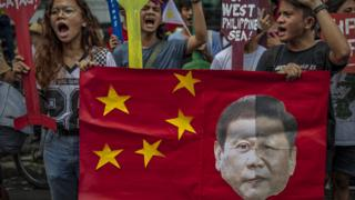 JULY 12: Filipinos hold a mock Chinese flag with a collage of the faces of Philippine President Rodrigo Duterte and Chinese President Xi Jinping during an anti-China protest outside the Chinese Embassy on July 12, 2019 in Makati, Metro Manila