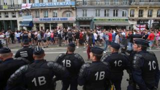 French police watch England fans outside a bar in Lille, on Wednesday 15 June during Euro 2016
