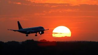 Avión con el sol de fondo.