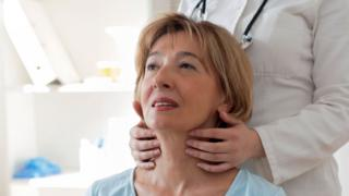 A woman having her throat examined by a doctor