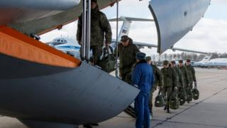 Russian defence ministry photos show army personnel boarding a flight to Italy in March