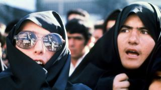 Heavily veiled Iranian women, one whose modern sunglasses reflect slogans and the Ayatollah Khomeini's portrait, demonstrate outside of the US Embassy, 29 November 1979.
