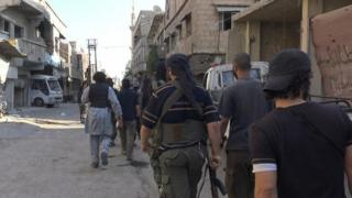 Photo published by pro-IS news agency, Amaq, purportedly showing jihadists on street in Qadam district of Damascus (30 August 2015)