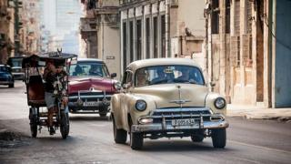 Old American cars are seen in a street of Havana
