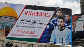 A picture taken on June 5, 2018, shows a poster erected on a main street in the West Bank town of Hebron next to a portrait of the Palestinian president Mahmud Abbas