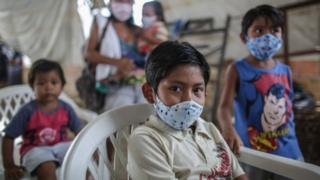 Indigenous boys wearing protective masks wait for vaccine and testing at Parque das Tribos community, on May 21 2020 in Manaus