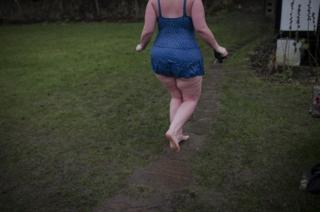 A woman walks on grass