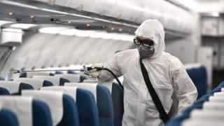 Man spraying plane with disinfectant