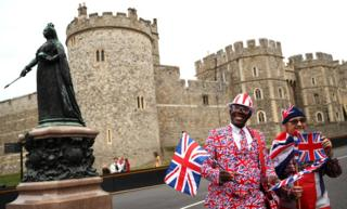 Royal fans Joseph Afrane and Sky London wave union jacks outside Windsor Castle on Thursday 11 October