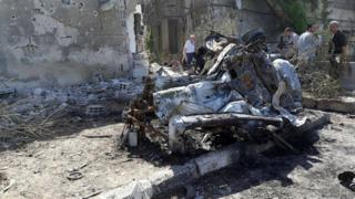People inspect the site of a car bomb blast in Damascus in this handout picture posted on SANA on July 2, 2017, Syria