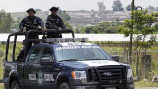 A unit of the Mexican Federal Police patrols the surroundings of the Puente Grande State prison (background) in Zapotlanejo, Jalisco State, Mexico, on 9 August,