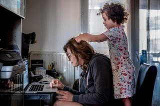 A woman uses a laptop whilst a child plays with her hair