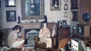 Dos mujeres sentadas debajo de una pintura de Mona Lisa colgando sobre la chimenea de un departamento de Londres de 1960.