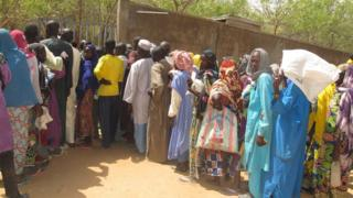 internally displaced people queue for camp inside Kolofata, wey dey north of Cameroon, for a food sharing wey International Red Cross Committee provide.