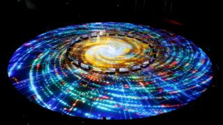 A light show is projected on the floor to look like the Milky Way galaxy