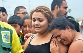 Relatives wanting information about their loved ones gather outside a beer distribution centre after it was attacked in the town of Garcia, on the outskirts of the northern city of Monterrey, Mexico, Friday, June 19, 2015