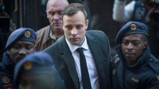 Oscar Pistorius arrives at court wearing a suit, flanked by two guards