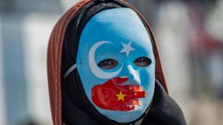 A protester against China's actions in Xinjiang wears a mask with the colours of the flag of East Turkestan
