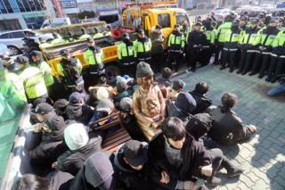 In this 28 December 2016, photo, members of civic groups sit around a comfort-woman statue after they set up in front of the Japanese consulate as police officers surround them in Busan, South Korea.