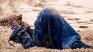 Una persona enterrando la cabeza en la arena
