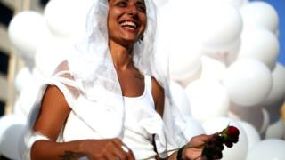 An activist from the Lebanese NGO Abaad (Dimensions), a resource centre for gender equality, dressed as a bride and wearing bandages, smiles while holding a rose as she celebrates in Beirut on August 17, 2017,