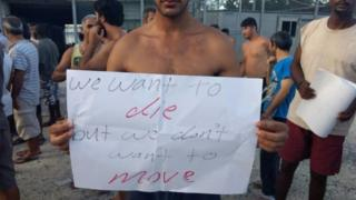 "A man in a detention camp holds a sign reading, ""We want to die, but we don't want to move""."