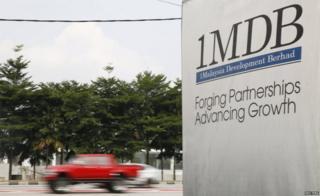 Traffic passes a 1Malaysia Development Berhad (1MDB) billboard at the Tun Razak Exchange development in Kuala Lumpur, Malaysia, 6 July 2015