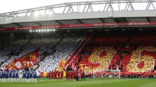 "Liverpool and Chelsea players observe a minute's silence on the pitch in front of fans displaying signs that spell out ""96"""