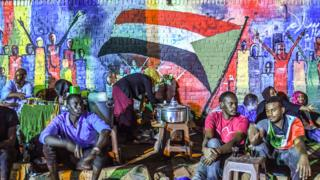 Sudanese protesters sit in front of a recently painted mural during a demonstration near the army headquarters in the capital Khartoum, Sudan - 24 April 2019