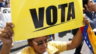 """An opposition supporter hold a placard that reads """"Vote"""" while she takes part in a rally against President Nicolas Maduro""""s government on University Student Day, in Caracas, November 21, 2015."""