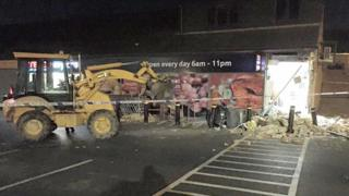 The stolen digger next to rubble at the Tesco store