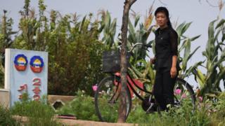一名朝鮮女子在新義州鴨綠江畔推著自行車而過(4/9/2017)